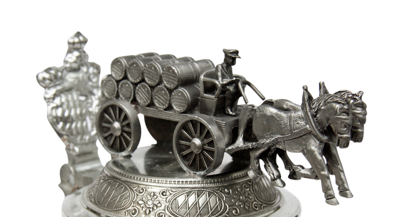 Ornate beer stein lid features a horse and carriage carrying