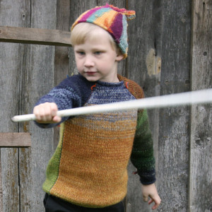 Summer Storm kids wool mohair raglan pullover sweater by Wrapture by Inese on boy with stick he is using like a play sword, also wearing a striped pixie gnome hat.