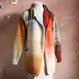 Liene Sweater Coat shown on dress form with dusty coral background wall in blue ivory orange brown Wrapture by Inese