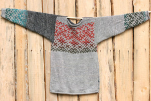 Latvian symbols sweater sweater hung flat on side of woodshed Wrapture by Inese