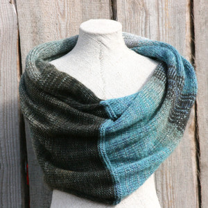 Fjord Edge shawl wrap on dress form in front of wood wall knit by Inese for Wrapture by Inese