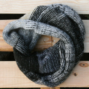 Black & white color way snood cowl flat on wood pallet background, knit by Inese Iris Liepina for Wrapture by Inese.