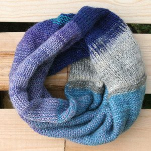 Catalonian Sea blue lavender color way snood cowl flat on wood pallet background, knit by Inese Iris Liepina for Wrapture by Inese.