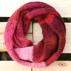 Cranberries red pink color way snood cowl flat on wood pallet background, knit by Inese Iris Liepina for Wrapture by Inese.
