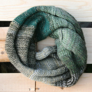 Forest Greens color way snood cowl flat on wood pallet background, knit by Inese Iris Liepina for Wrapture by Inese.