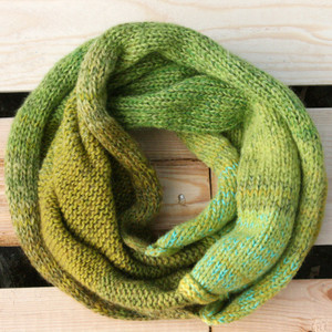 Greens color way snood cowl flat on wood pallet background, knit by Inese Iris Liepina for Wrapture by Inese.