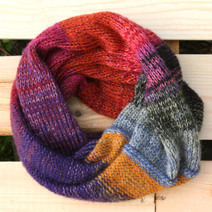 Midsummer Fire color way snood cowl flat on wood pallet background, knit by Inese Iris Liepina for Wrapture by Inese.