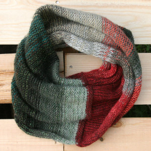 Winter Apples color way snood cowl flat on wood pallet background, knit by Inese Iris Liepina for Wrapture by Inese.