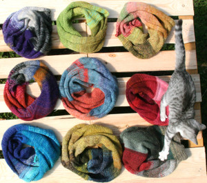 9 cowls on wood pallet with kitten, knit by Wrapture by Inese