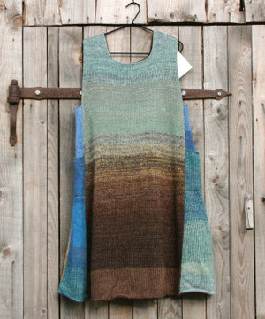 South Island  trapeze dress on coathanger hung on woodshed door knit by Inese iris Liepina of Wrapture by Inese