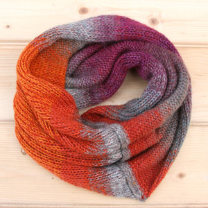 Gerberas color way snood cowl flat on wood pallet background, knit by Inese Iris Liepina for Wrapture by Inese.