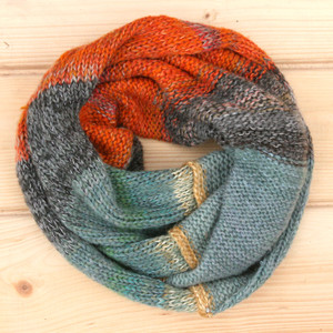 Sunset color way snood cowl flat on wood pallet background, knit by Inese Iris Liepina for Wrapture by Inese.