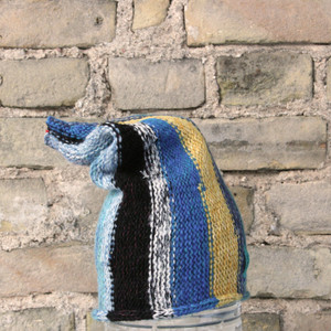 Blue Skies S/M pixie gnome hat knit by Wrapture by Inese in front of brick wall