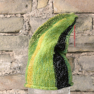 Billie S/M pixie gnome hat knit by Wrapture by Inese in front of brick wall