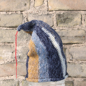 Denim S/M pixie gnome hat knit by Wrapture by Inese in front of brick wall