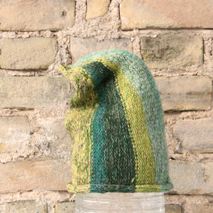 forest S/M pixie gnome hat knit by Wrapture by Inese in front of brick wall