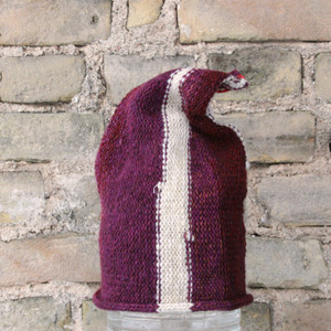 Latvia S/M pixie gnome hat knit by Wrapture by Inese in front of brick wall