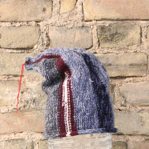 Latvian Sky S/M pixie gnome hat knit by Wrapture by Inese in front of brick wall