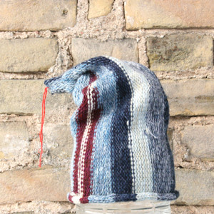 Latvian star S/M pixie gnome hat knit by Wrapture by Inese in front of brick wall