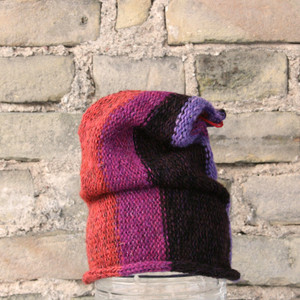 Magenta S/M pixie gnome hat knit by Wrapture by Inese in front of brick wall
