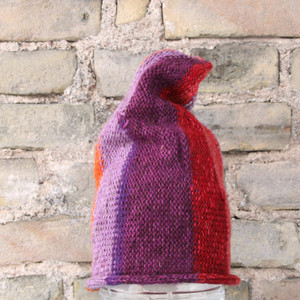 Orange Violet S/M pixie gnome hat knit by Wrapture by Inese in front of brick wall