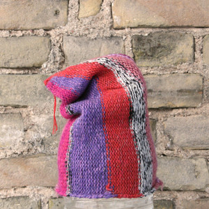 Pink S/M pixie gnome hat knit by Wrapture by Inese in front of brick wall