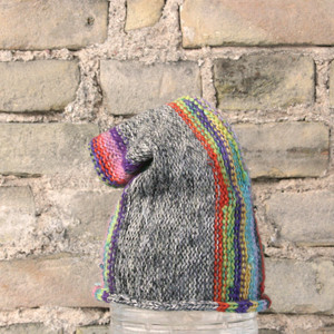 Rainbow S/M pixie gnome hat knit by Wrapture by Inese in front of brick wall