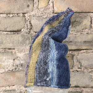 Seashore S/M pixie gnome hat knit by Wrapture by Inese in front of brick wall