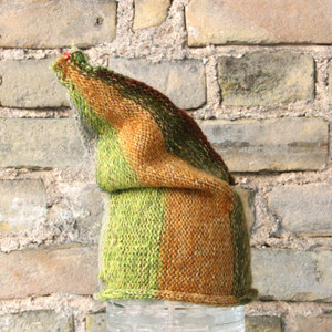 Spring Greens S/M pixie gnome hat knit by Wrapture by Inese in front of brick wall