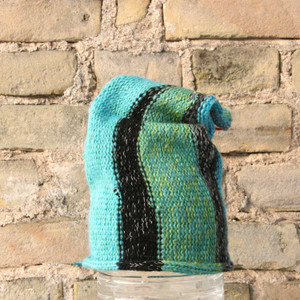 Turquoise Black S/M pixie gnome hat knit by Wrapture by Inese in front of brick wall