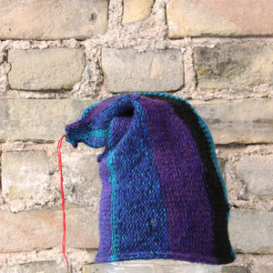 Twilight Zone S/M pixie gnome hat knit by Wrapture by Inese in front of brick wall
