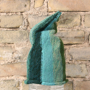 Willow S/M pixie gnome hat knit by Wrapture by Inese in front of brick wall