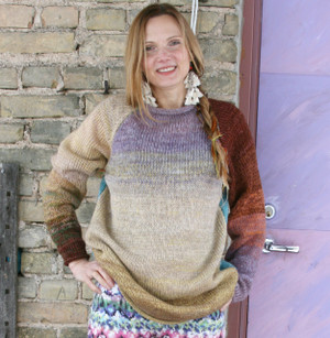 Fragments turquoise blue gold brown lavender size M reversible raglan pullover where the sweater is worn by a model in front of a brick wall with a purple door, designed and knit by Wrapture by Inese