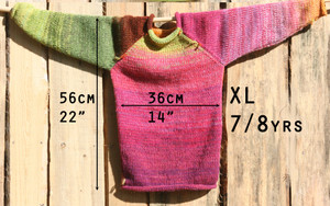 Measurement chart for kids XL, 7/8 year raglan sweater with pink sweater hung on a wood shed.