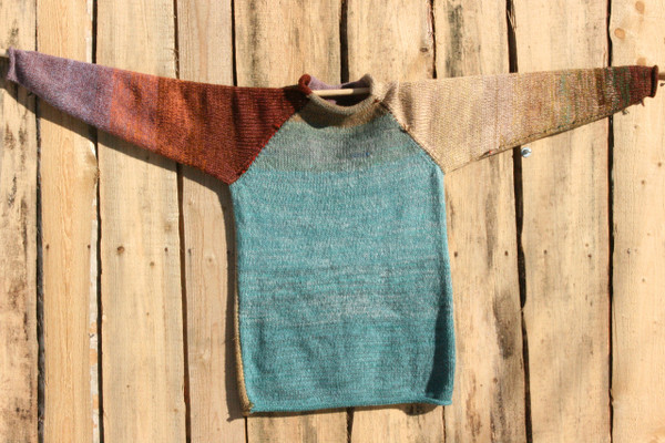 Fragments unisex reversible raglan pullover sweater on wood shed