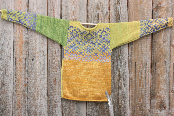 Chartreuse Green Latvian symbols reversible unisex sweater knit by Wrapture by Inese and hung flat on side of woodshed size M
