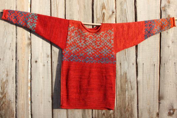 Uguns un Nakts Latvian symbols sweater hung flat on side of woodshed size L