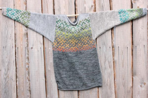 Grey Forest Latvian symbols sweater flat on side of woodshed size L