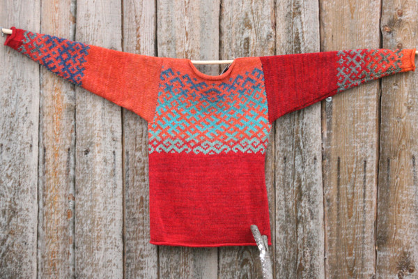 Reversible unisex red orange Latvian symbols sweater size M knit and designed by Inese hung flat on a wood shed wall