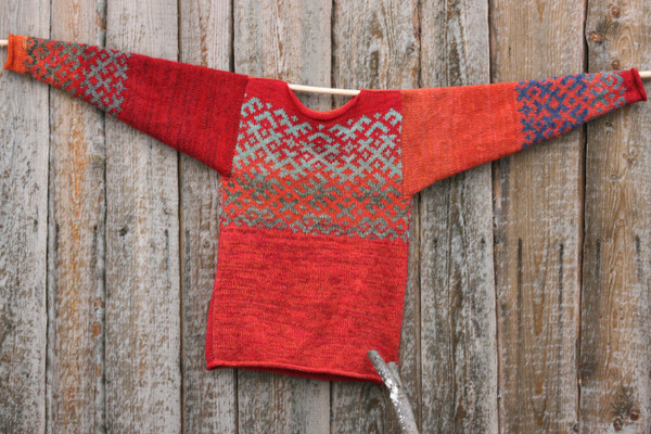 Reversible unisex red orange Latvian symbols sweater size M knit and designed by Inese hung flat on a wood shed wal