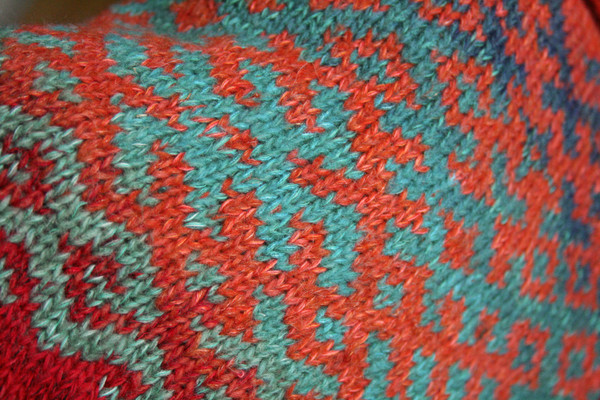 closeup of red orange Latvian symbols  designed by Inese and knit with wool, kid mohair, silk, cotton