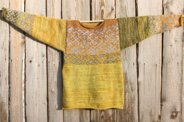 one side of reversible mustard yellow Latvian symbols sweater flat on side of woodshed size L knit by Inese Iris Liepina