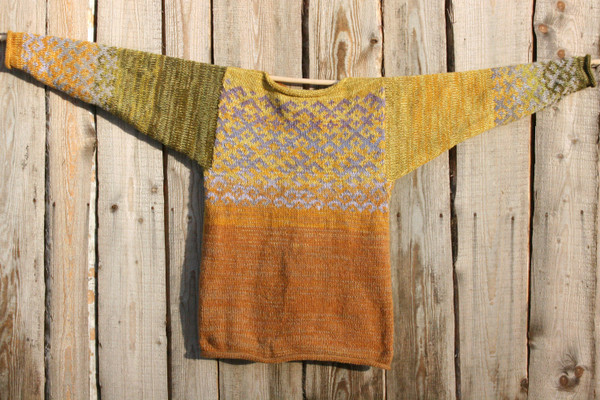 one side of reversible mustard yellow Latvian symbols sweater flat on side of woodshed size L