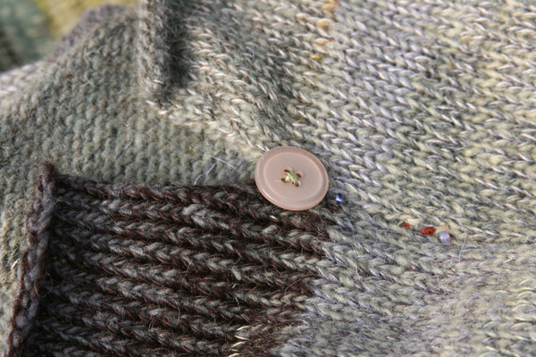 detail of ombre color change showing rolled hem, side slit and decorative button on knit Grey Leaves dress, knit by Inese Iris Liepina of Wrapture by Inese