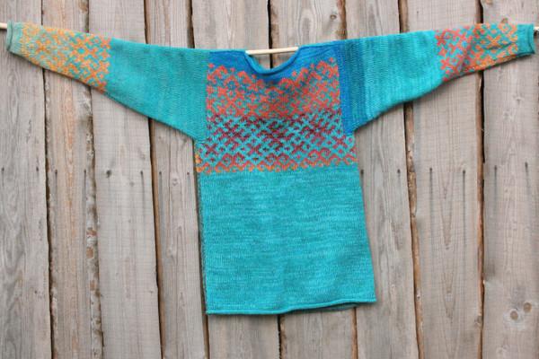 Turquoise blue Latvian symbols reversible sweater flat on side of woodshed size L