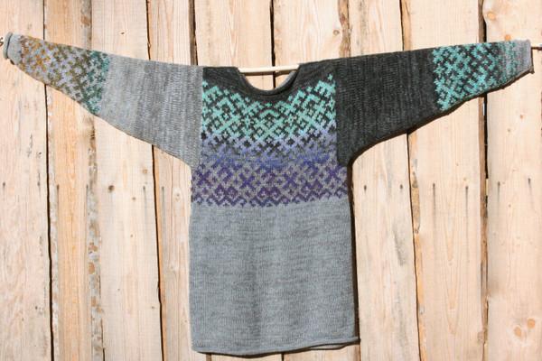 Heather Grey Latvian symbols sweater flat on side of woodshed size L