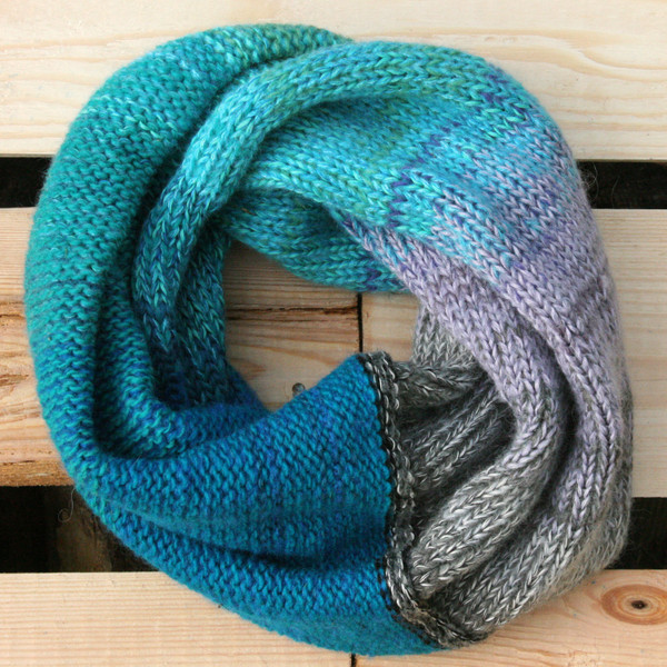 Winter Glow color way snood cowl flat on wood pallet background, knit by Inese Iris Liepina for Wrapture by Inese.