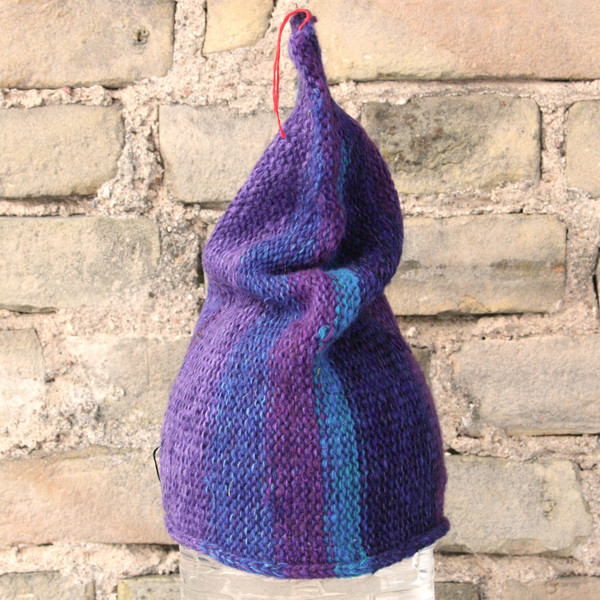 Twilight S/M pixie gnome hat knit by Wrapture by Inese in front of brick wall