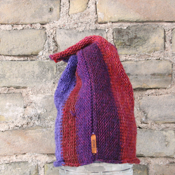 Violet S/M pixie gnome hat knit by Wrapture by Inese in front of brick wall
