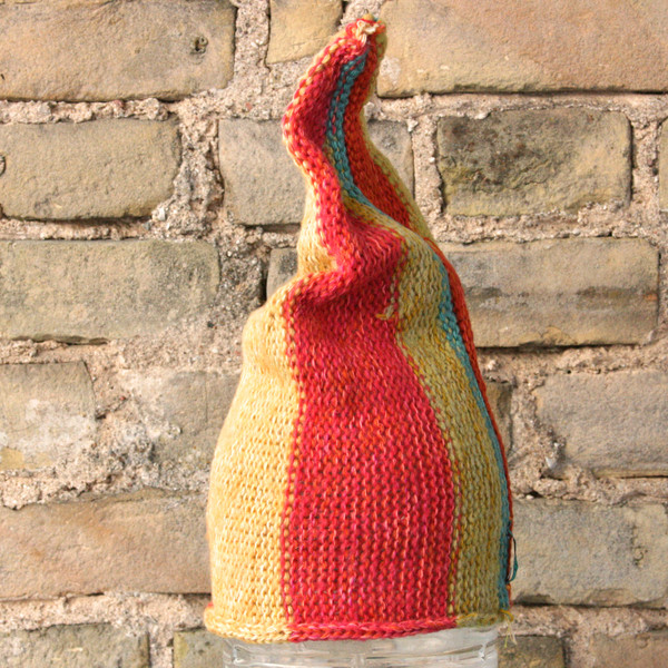 Yellow Stripe  S/M pixie gnome hat knit by Wrapture by Inese in front of brick wall